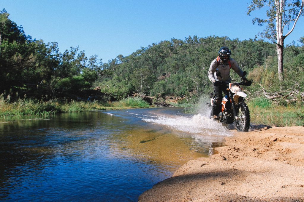 2015 KTM 690 offroad riding through a river